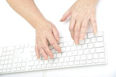 Руки старой женщины печатая на машинке на клавиатуре Стоковая Фотография