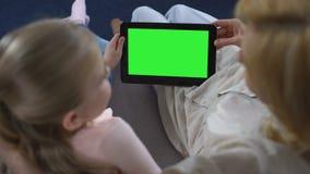 Руки старухи и маленькой девочки держа таблетку с зеленым экраном, наблюдая видео видеоматериал