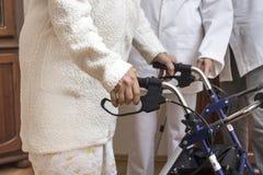 Руки старухи на ручках ходока с тормозами Медсестра помогает старухе стоковое изображение rf