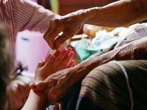 Руки старухи развевая белый грех вокруг ее рук внучки - тайское традиционное благословение Sai строки от старейшины одного стоковые изображения rf