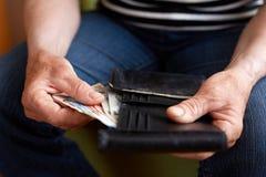 Руки старшей женщины держа деньги Стоковое Фото