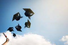 Руки студент-выпускников бросая шляпы градации Стоковая Фотография
