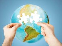 Руки с белой пустой головоломкой над глобусом земли Стоковая Фотография RF