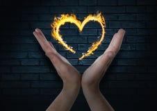 руки с значком огня сердца сверх Темная предпосылка стены кирпичей Стоковое фото RF