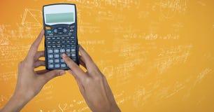 Руки с калькулятором против желтых doodles математики Стоковые Фото