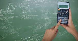 Руки с калькулятором против зеленой доски с математикой doodles Стоковые Фото