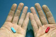 Руки с красным цветом и синью капсулы Стоковое Изображение