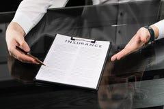 Руки с ручкой и страхование на таблице стоковая фотография
