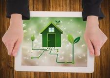 Руки с таблеткой на таблице показывая график зеленого дома против bokeh Стоковое Изображение RF