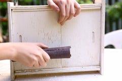 Руки с шкуркой подготавливают старую мебель Стоковые Фотографии RF