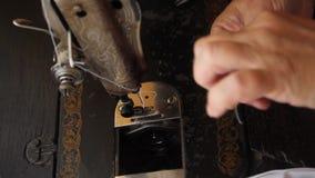 Руки ткани старухи scribbling белой на старой ручной швейной машине Двойная обработка края ткани края катушка сток-видео