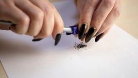 Руки точить карандаш и shavings на белом листе бумаги видеоматериал