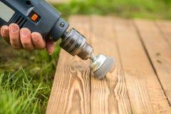 Руки укомплектовывают личным составом при электрический вращая диск металла щетки зашкурить кусок дерева Стоковая Фотография