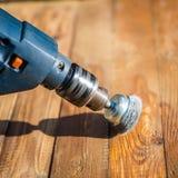 Руки укомплектовывают личным составом при электрический вращая диск металла щетки зашкурить кусок дерева Стоковое Изображение