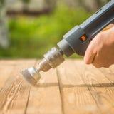 Руки укомплектовывают личным составом при электрический вращая диск металла щетки зашкурить кусок дерева Стоковое Фото