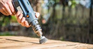 Руки укомплектовывают личным составом при электрический вращая диск металла щетки зашкурить кусок дерева Стоковые Изображения RF