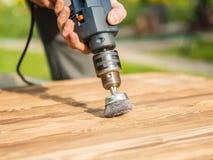 Руки укомплектовывают личным составом при электрический вращая диск металла щетки зашкурить кусок дерева Стоковые Фото