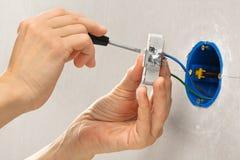 Руки устанавливая электрическую стенную розетку с отверткой Стоковое фото RF