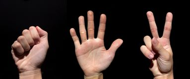 Руки утеса, бумаги и ножниц на изолированной черной предпосылке стоковое фото