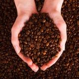 руки фасолей приданные форму чашки кофе вне Стоковые Фото