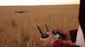 Руки фермера держат удаленный регулятор с его руками пока quadcopter летает на предпосылку Трутень завишет мухы прочь видеоматериал