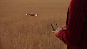 Руки фермера держат удаленный регулятор с его руками пока quadcopter летает на предпосылку Трутень завишет за акции видеоматериалы