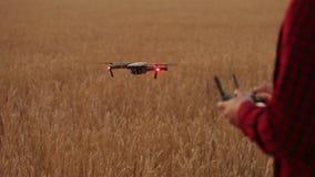 Руки фермера держат удаленный регулятор с его руками пока quadcopter летает на предпосылку Трутень завишет за видеоматериал