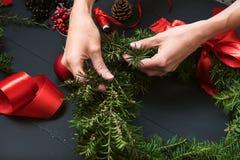 Руки флориста делая венок рождества Стоковые Изображения RF