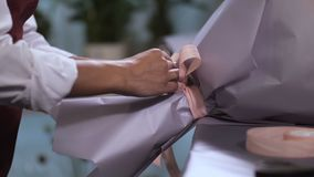 Руки флориста делая украшение ленты для букета видеоматериал