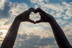 Руки формируя сердце - распространите влюбленность стоковая фотография