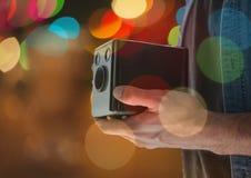руки фотографа с винтажной камерой на ноче Света запачканные цветом позади и перекрытие Стоковое Изображение
