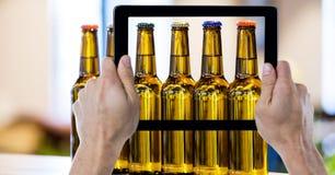 Руки фотографируя пивные бутылки через цифровую таблетку на баре Стоковые Фотографии RF