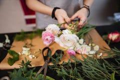 Руки флориста женщины создавая букет с розовыми розами Стоковые Фото