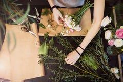Руки флориста женщины создавая букет цветка на таблице Стоковая Фотография RF