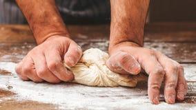 Руки хлеба замешивают хлебопека теста варя курсы стоковая фотография