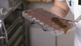 Руки хлебопека извлекают сверхнормальный шоколад со шпателем из формы видеоматериал
