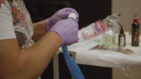 Руки художника татуировки подготавливая машину татуировки для татуировать сток-видео