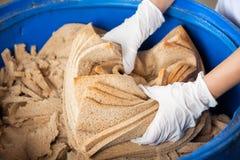 Руки хлебопека сбрасывая отход хлеба в мусорном ведре Стоковая Фотография