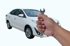 Руки человека автоматического механика держат ключ и ключ колеса стоковое изображение