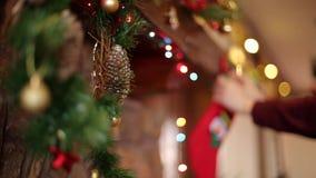 Руки человека вися чулок или носок рождества над камином украшенным с красочными проблескивая светами и венком гирлянды акции видеоматериалы