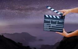 Руки человека держа колотушку фильма на млечном пути, звездах и горах Показанная доска шифера используйте цвета белые и черные Ре иллюстрация вектора