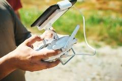 Руки человека держа трутня quadrocopter с дистанционным управлением стоковые изображения