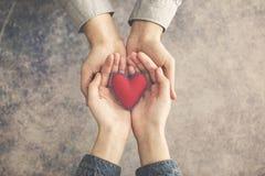 Руки человека и женщины вместе с красным сердцем стоковые изображения