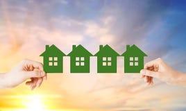 Руки человека и женщины с много домов зеленой книги Стоковые Фото