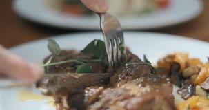 Руки человека отрезаны с ножом конец-вверх стейка мяса Кто-то еда жирной калорийной пищи в ресторане акции видеоматериалы