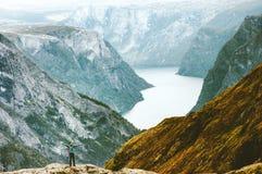 Руки человека поднятые исследователем на горах Naeroyfjord стоковые изображения