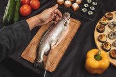Руки человека режа филе рыб в ресторане стоковое фото rf