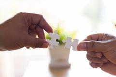 Руки человека соединяя часть головоломки пар стоковое изображение rf