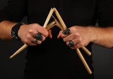 Руки человека с сломленными drumsticks над чернотой стоковые фото