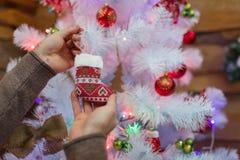Руки человека украшают рождественскую елку с игрушкой в форме ботинка indoors Стоковые Фотографии RF
